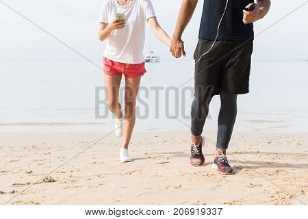 Unrecognizable Couple Of Runners Holding Hands Use Cell Smart Phones Man And Woman Sport Runners On Beach Working Out Mix Race Male And Female Fitness Jogger On Seaside Together
