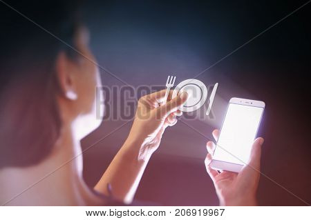 Image of a woman with a smartphone in her hand. She holds restaurant icon. Concept of modern technology in catering industry.