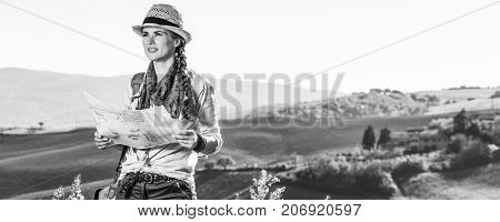 Discovering magical views of Tuscany. adventure woman hiker with bag hiking in Tuscany with map looking into the distance