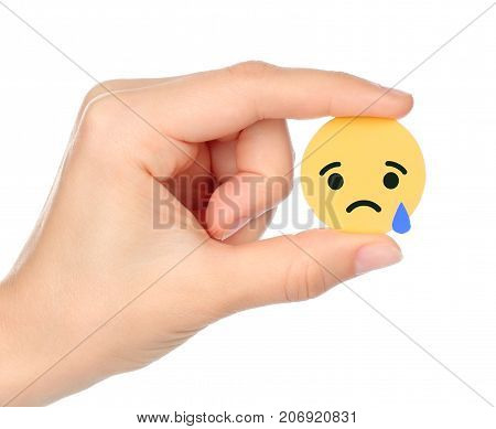 Kiev Ukraine - September 04 2017: Hand holds Facebook Sad Empathetic Emoji Reaction printed on paper. Facebook is a well-known social networking service