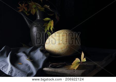 melon on a silver platter with a bouquet of autumn leaves