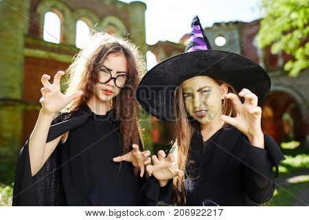 Frightening little witches in black warlocks at halloween party