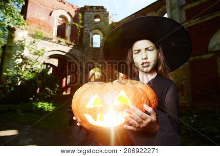 Halloween little girl in black hat and warlock holding jack-o-lantern
