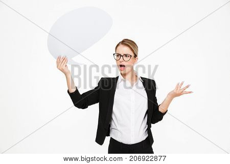 Displeased blonde businesswoman in eyeglasses looking aside and holding blank speech bubble over white background