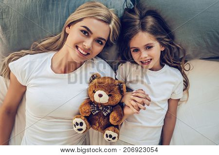 Attractive young woman and her little cute daughter are spending time together. Top view of mom with daughter are lying on bed with plush toy and smiling.