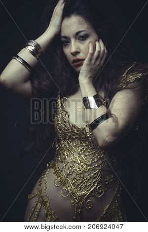 Fashion, Girl in dress made of golden threads with golden mask, beautiful young brunette