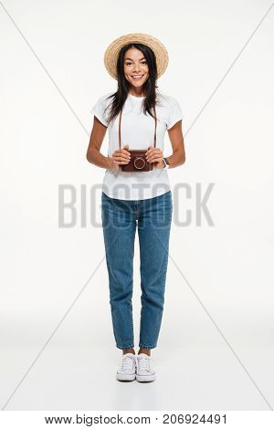 Full length portrait of a smiling young woman in hat standing and holding camera isolated over white background