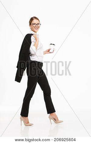 Full length side view image of smiling blonde business woman in eyeglasses walking in studio with cup of coffee and looking at the camera over white background