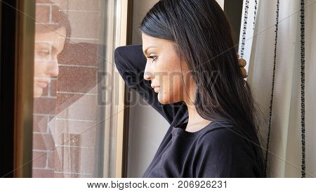 Close up of Face of a Pensive Pretty Depressed Young Woman, Looking Down by a Window, Worried or Sad.