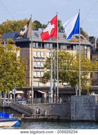Zurich, Switzerland - 29 September, 2017: flags of Zurich Film Festival, Switzerland and Zurich at Quaibrucke bridge, buildings at the Bellevue square in the background. Zurich Film Festival takes place annually at the end of September.
