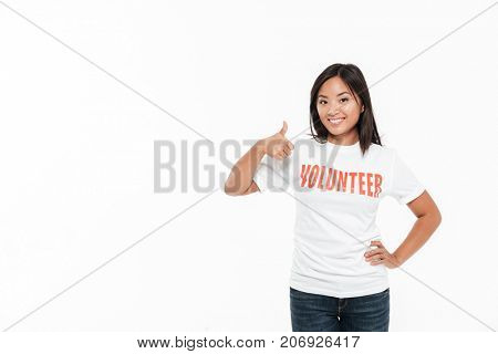 Portrait of a happy satisfied asian woman in volunteer t-shirt standing and showing thumbs up gesture with a big copy space isolated over white background