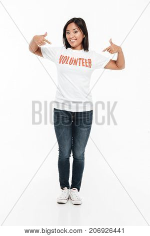 Full length portrait of a happy young asian woman in volunteer t-shirt standing and pointing two fingers while looking at camera isolated over white background