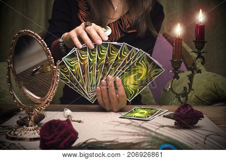 Tarot cards in fortune teller woman hands. Paranormal table.