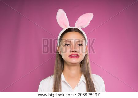 a girl in pink ears disappointed with the taste of her chewing gum