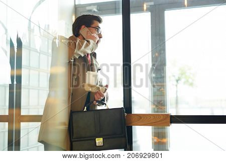 Busy man with briefcase and hot drink talking by mobile phone while leaving cafe