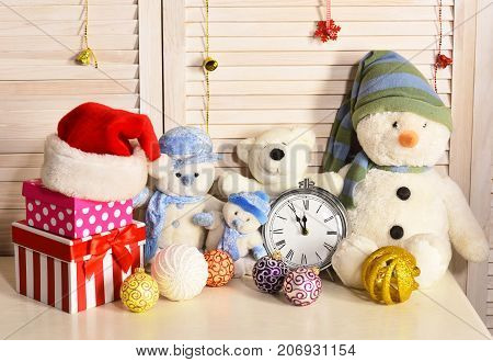 Toys placed on bureau on wooden wall background. Celebration and New Year decor concept. Christmas decorations in festive room. Snowmen teddy bears Christmas balls and present boxes near alarm clock