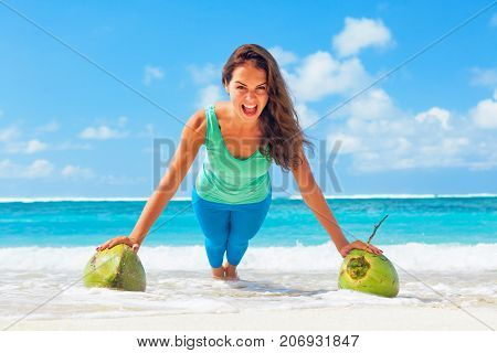 Active woman doing fitness exercise plank on coconut to keep fit and health. Beach surf background. Healthy lifestyle morning workout sport activity on summer family vacation in tropical island.