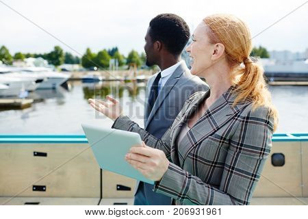 Contemporary business partners discussing view from their steamship
