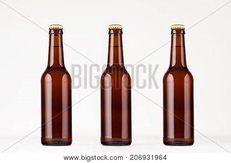 Three brown longneck beer bottle 330ml mock up. Template on white wood table.