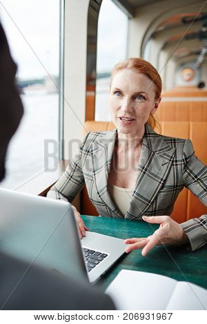 Middle aged businesswoman and her colleague brainstorming and discussing ideas at start-up meeting