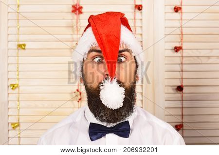 Santa Claus In Red Hat With Grimace. Man With Beard