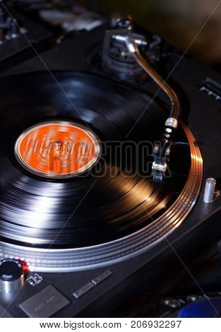 Dj turntables needle cartridge on black vinyl record with music. Close up, nobody, focus on turntable and audio disc record