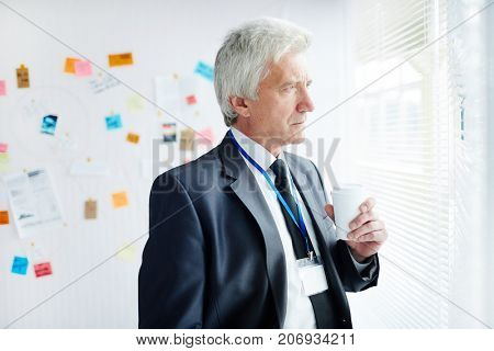 Profile view of pensive senior FBI agent with paper cup of coffee in hand looking out office window while thinking over motive of committed crime, waist-up portrait shot
