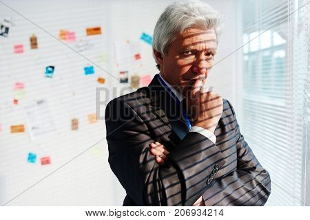 Pensive mature FBI agent rubbing his chin while thinking over committed crime, investigation board with collected evidence on background, portrait shot