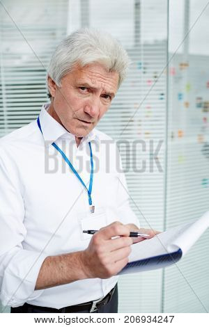 Portrait of mature FBI agent posing for photography with frowning face while taking necessary notes on clipboard, glass wall on background