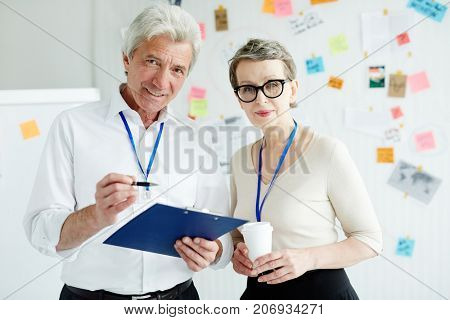 Talented members of homicide department looking at camera while having working meeting at open plan office, investigation board with collected evidence on background