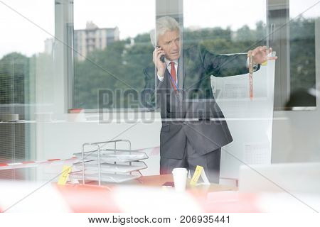 Mature crime scene investigator in classic suit calling to his colleague after finding out bloodstained knife at crime site, view through panoramic window