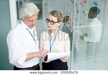 Mature forensic examiner showing results of criminalistic examination to concentrated FBI agent while standing at open plan office