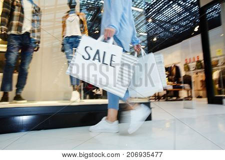 Sale paperbags carried by hurrying shopper choosing new stylish clothes on black friday