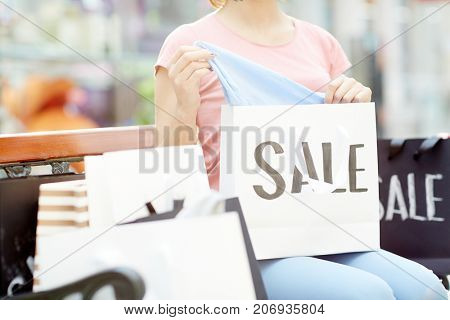 Young modern shopper looking through paperbags with new trendy clothes bought in the mall