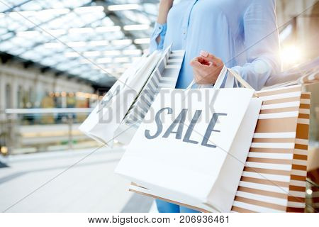 Young customer holding sale paperbags while shopping in trade center on black friday