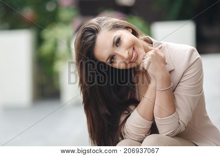 Bright portrait of beautiful brunette woman with long straight hair,long eyelashes,grey eyes,light makeup,nice smile,white straight teeth,dressed in a beige Trouser suit, posing sitting outdoors on one of the streets in the spring