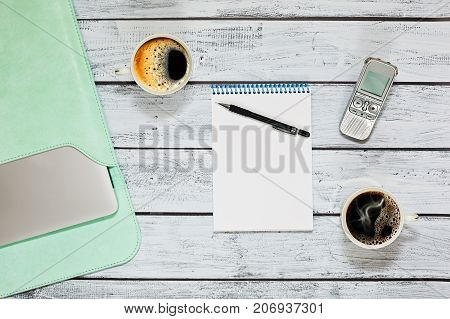 Taking an interview while having a coffee break - top view capture with two cups of coffee on wooden table in loft style notepad with place for text dictaphone and a laptop in leather cover.