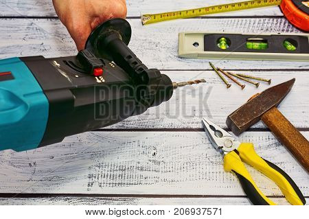 Workshop Concept - Hand Tools And A Perforator In Hand