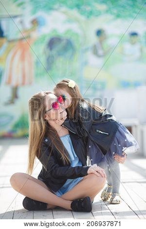 A happy family, mom - a young pregnant woman with blond hair and her little daughter, a 5 year old girl with blond hair, both dressed in black leather jackets, spending time together outdoors in summer on a sunny day, both wearing sun glasses