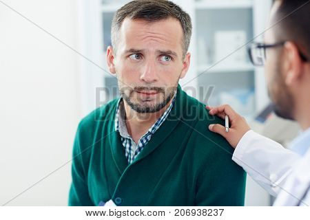 Head and shoulders portrait of upset middle-aged patient listening to his physician with concentration while he trying to put him at his ease