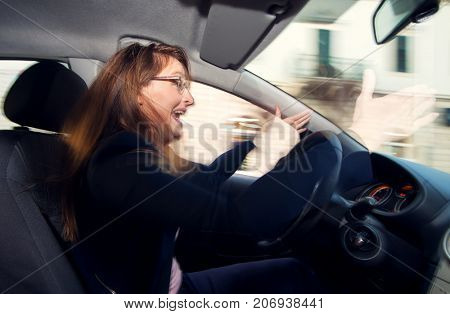 Nervous and bad tempered female driver yelling at other drivers in traffic