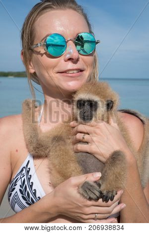 Portrait of smiling woman in sunglasses holding gibbon monkey on the beach over blue sea and sky background