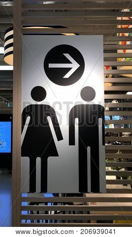 Modern man and woman toilet sign on wooden partition in public area