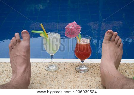 Closeup of cocktails and male's feet at the edge of the outdoor swimming pool