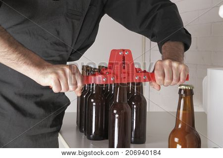 Homebrewing: closing the bottles with a bottle capper.