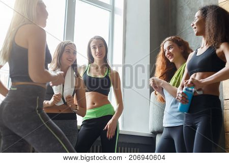 Girls in sportswear chatting before dancing class. Group of young fit female friends at sport club, pov. Active and healthy lifestyle concept