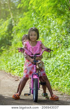 NAN THAILAND - OCT 24 : Asian Undefined happy girls riding bicycle on the street of countryside at BaanPaknai on October 24 2016 in Nan province Thailand