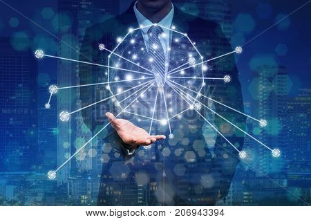 Businessman hand holding the Futuristic Technology connection shape over the network connection and the building cityscape on dark background business technology and Social Network concept, 3D illustration