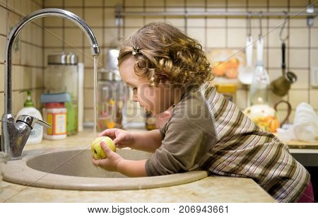 A cute two-year girl washes an apple in a sink in the kitchen