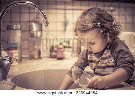 A cute two-year girl is washing dishes in the kitchen